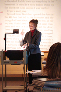 Woman talking and standing next to overhead projector, with projected text in background.