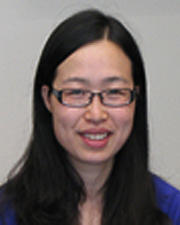 Woman with dark, long hair, dark-rimmed eyeglasses, and a blue shirt.