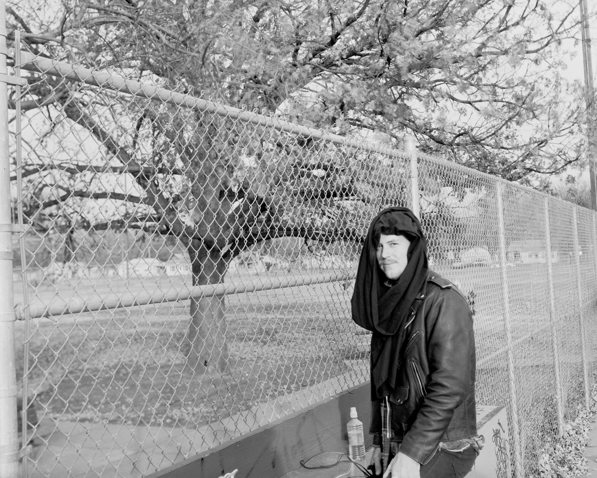 Boy standing outside by a fence.