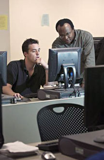 a student and professor working on a computer
