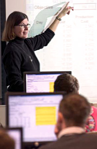 Woman with glasses pointing at projected image, talking to class, with students at computers in foreground.